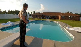 (MSMCC101) Pike County, Mississippi. Pike County Sheriff's Deputy Jason Powell Pike County sheriff's deputy Jason Powell stands next to the pool where two men drowned at a home on Old Highway 24 Extension in eastern Pike County Mississippi on Saturday May 12, 2007. Johnny McEwen, 59, drowned trying to save Cody Coney, 32, during a family gathering.(Ap Photo, The Enterprise-Journal, Aaron Rhoads